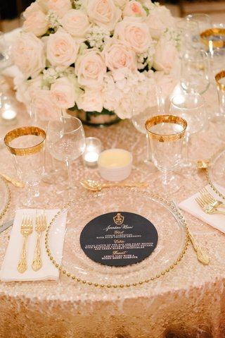 navy-blue-round-menu-design-with-gold-and-white-calligraphy-monogram-sequin-tablecloth-low-flowers