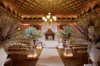 gold-wedding-ballroom-paneling-with-white-delphinium-flowers-along-aisle
