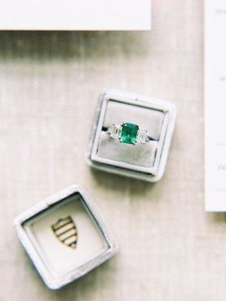 wedding-ring-in-grey-box-with-crest-three-stone-ring-with-emerald-center-stone-two-side-stones