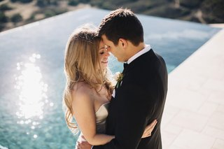 blonde-bride-with-hair-down-hugging-groom-in-tux-in-front-of-infinity-pool