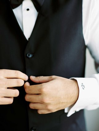groom-buttoning-up-black-tuxedo-vest-with-black-three-letter-monogram-on-white-shirt-cuff