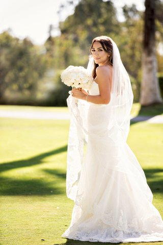 bride-in-wedding-dress-and-cathedral-length-veil-with-bouquet-of-white-flowers