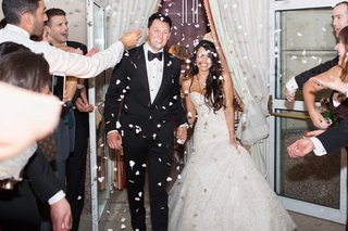 newlyweds-exit-guests-throw-confetti-on-them-trumpet-wedding-gown-black-tuxedo