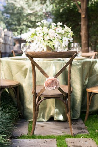 rustic-wooden-chair-with-pink-flower-rosette-and-green-table-linens-with-lush-floral-arrangement