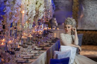 bride-with-large-headpiece-and-beaded-dress-sitting-at-white-chair-cover-long-table-styled-shoot