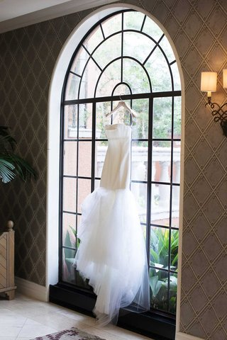 vera-wang-strapless-wedding-dress-hanging-in-black-frame-arch-window-of-venue-tulle-skirt