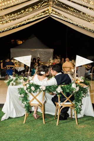 wedding-reception-tent-sweetheart-table-bride-groom-kiss-flags-garland-white-blush-flowers-kiss