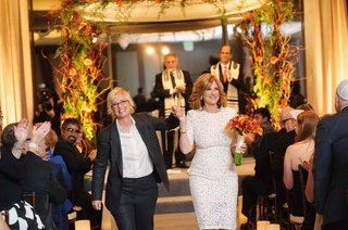 lori-wolf-in-bridal-suit-walking-down-aisle-with-carol-leifer-in-white-lace-dress-orange-bouquet