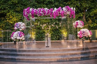 clear-translucent-lucite-ceremony-arch-with-purple-orchid-flowers-and-lucite-flower-stands