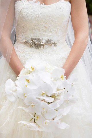 bride-holds-cascading-bouquet-of-white-orchids-in-her-white-bridal-ball-gown-vera-wang