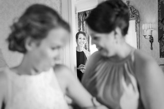 black-and-white-photo-of-mother-of-bride-watching-bride-get-her-wedding-dress-on-with-bridesmaid