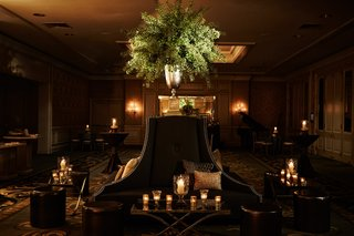 settees-and-banquettes-at-wedding-reception-ballroom-tall-greenery-arrangements-candlelight