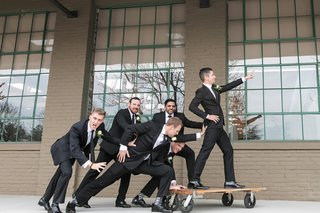 groom-and-groomsmen-in-black-suits-playful-pose-riding-on-dolly