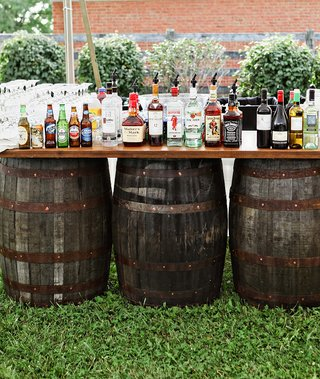farm-wedding-reception-with-a-rustic-bar-set-on-old-barrels