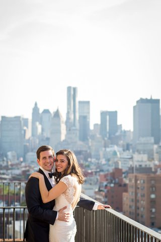 wedding-couple-in-tuxedo-and-gown-from-mark-ingram-atelier-on-rooftop-balcony-with-view-of-city
