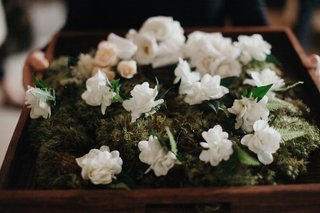 boutonniere-on-bed-of-moss-white-flowers-ferns-greenery