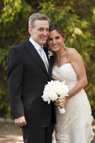 bride-in-a-strapless-romona-keveza-gown-and-white-bouquet-with-groom-in-a-black-tuxedo