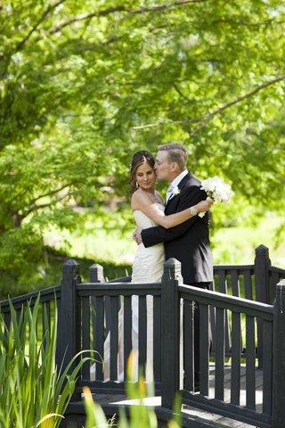groom-in-a-black-tuxedo-kisses-bride