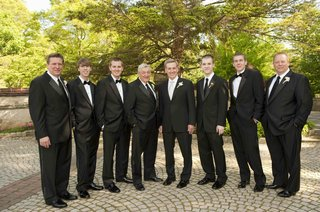 groom-and-groomsmen-in-black-tuxedos-and-ties-and-bow-ties