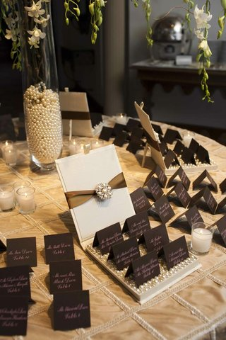 place-card-table-covered-with-a-golden-tablecloth-and-topped-with-chocolate-brown-place-cards