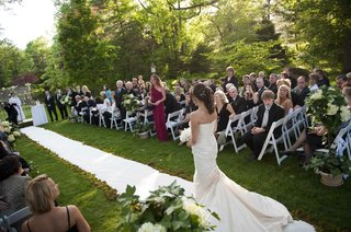 bride-walks-down-the-aisle-of-an-outdoor-ceremony-in-a-ruched-romona-keveza-gown