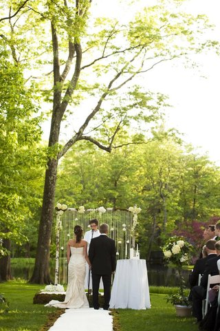 bride-in-a-romona-keveza-dress-with-groom-in-a-black-tuxedo-in-an-outdoor-wedding-ceremony