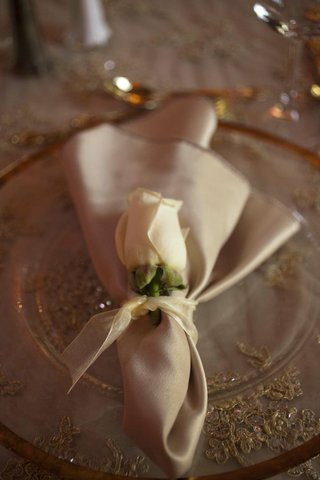 wedding-reception-place-setting-with-a-clear-gold-rimmed-charger-gold-napkin-and-white-rose