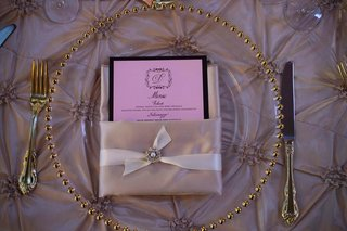 wedding-reception-place-setting-with-a-clear-charger-with-beaded-golden-rim-and-pink-linens