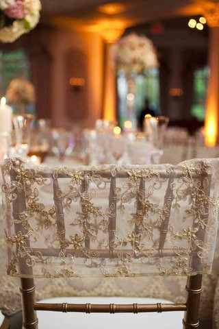 golden-chair-with-an-embroidered-and-beaded-sleeve-at-a-wedding-reception