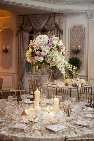 wedding-reception-centerpiece-of-white-green-pink-and-light-purple-flowers-in-a-tall-glass-vase