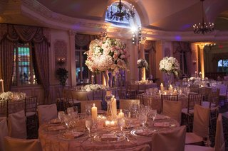 wedding-reception-centerpiece-of-white-green-pink-purple-flowers-in-a-tall-glass-vase