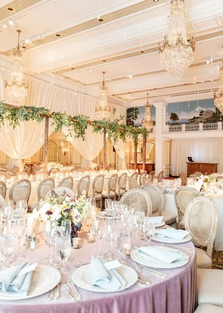 wedding-reception-ballroom-chandelier-round-table-lavender-linen-oval-back-wood-cane-chairs-greenery