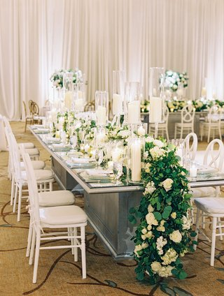 wedding-reception-mirror-long-table-with-white-chairs-candles-and-flower-greenery-runner-overflowing