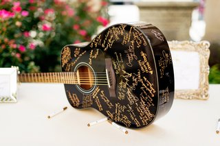 black-acoustic-guitar-with-gold-signatures-for-wedding-guest-book