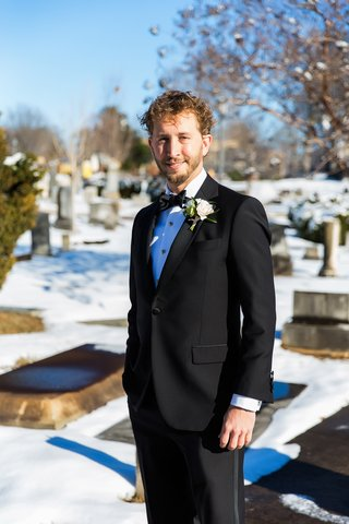 groom-in-brooks-brothers-tuxedo-hand-in-pocket-snow-covered-cemetary