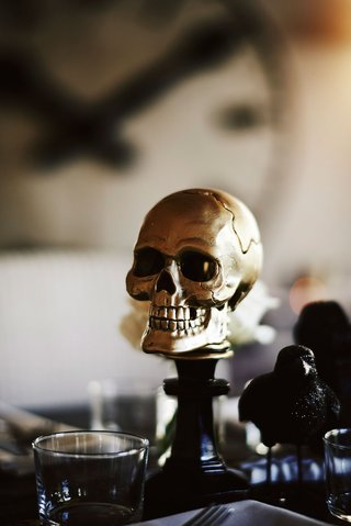 halloween-wedding-ideas-gold-skull-on-top-of-candlestick-and-black-raven-crow