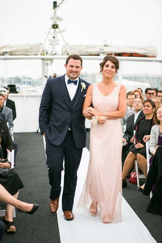 groom-in-navy-joseph-abboud-suit-escorted-by-mother-in-blush-gown-on-yacht-wedding