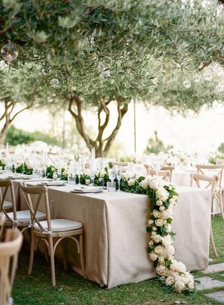 wedding-reception-long-reception-table-vineyard-chairs-greenery-garland-white-flowers-trees-orbs