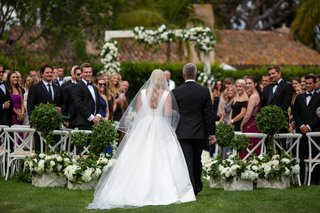 wedding ceremony outdoor garden greenery white decor back of bride and dad walking down aisle