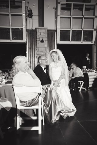bride-sits-with-family-at-reception