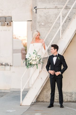 bride-in-white-off-the-shoulder-wedding-dress-white-bouquet-groom-in-suit-bow-tie-on-staircase
