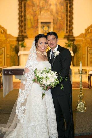bride-groom-pose-catholic-church-long-traditional-veil-necklace-tuxedo-tie-wedding-california