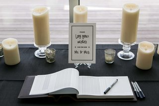 a-guest-book-ceremony-for-well-wishes-on-black-tablescape-with-low-candles