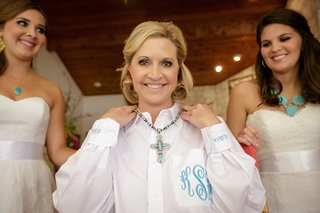 bride-putting-on-necklace-with-turquoise-cross-with-bridesmaid-necklaces