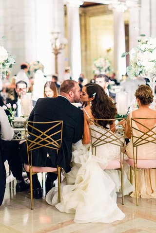 A Charming Fete Couple's Kiss at Head Table gold chairs pink decor