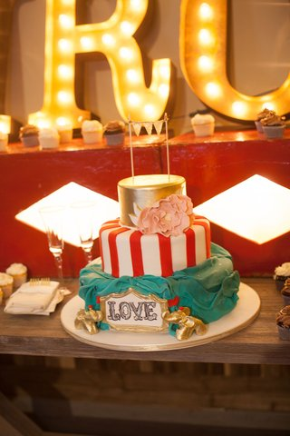 red-and-white-stripe-circus-tent-cake-with-gold-top-tier-sugar-flower-banner-gold-elephants-at-base