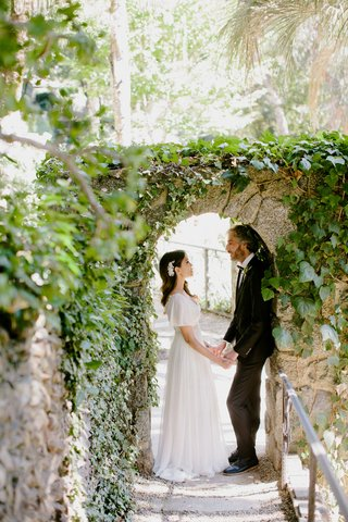 bride-in-boho-dress-with-pretty-headpiece-holding-hands-with-groom-under-stone-arch-greenery-boho