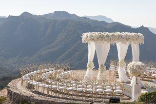 wedding ceremony on helipad at malibu rocky oaks vineyard estate white drapery and flowers gold