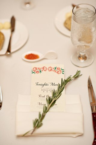 wedding-reception-with-menu-decorated-with-pink-flowers-in-cream-napkin-rosemary-sprig