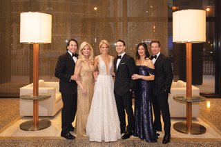 bride in plunging neckline berta wedding dress with groom parents in eveningwear mothers in sequin gowns